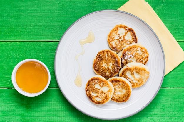 Panquecas de queijo caseiro com mel num prato sobre uma mesa de madeira. vista do topo