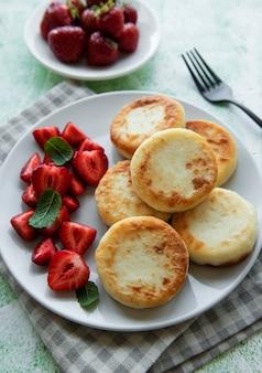 Panquecas de queijo cottage bolinhos de ricota em prato de cerâmica com morango fresco