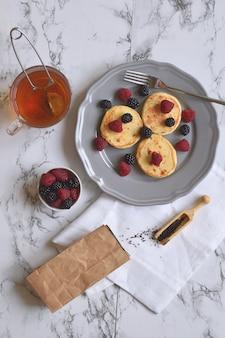 Panquecas de queijo cottage café da manhã saudável sem glúten framboesa amora folha de chá caneca de mármore vista superior vista plana
