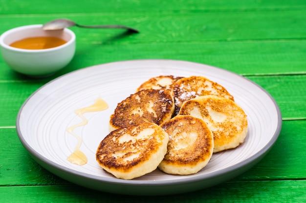 Panquecas de queijo cottage caseiro com mel em um prato sobre uma mesa de madeira