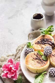 Panquecas de queijo cottage com amoras, chocolate e menta. syrniki. café da manhã gourmet.