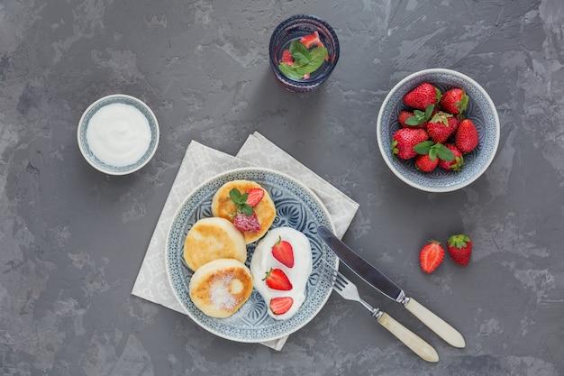 Panquecas de queijo cottage com creme de leite e morangos no café da manhã ou almoço no cinza. vista do topo
