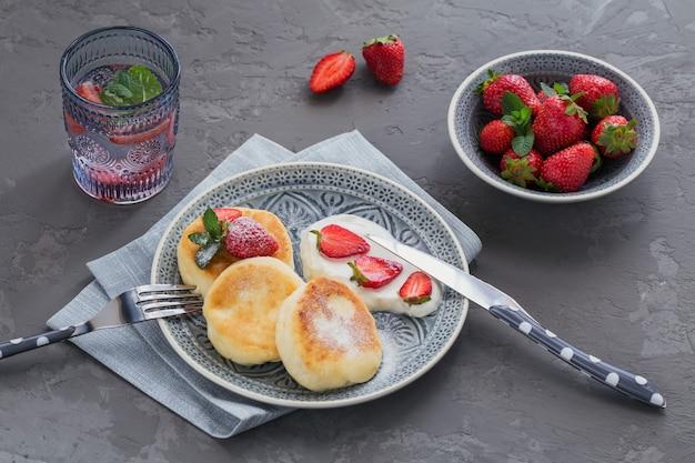 Panquecas de queijo cottage com creme de leite e morangos no café da manhã ou almoço no cinza.