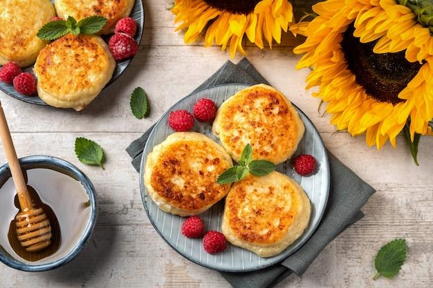 Panquecas de queijo cottage com framboesas e folhas de hortelã em um prato.