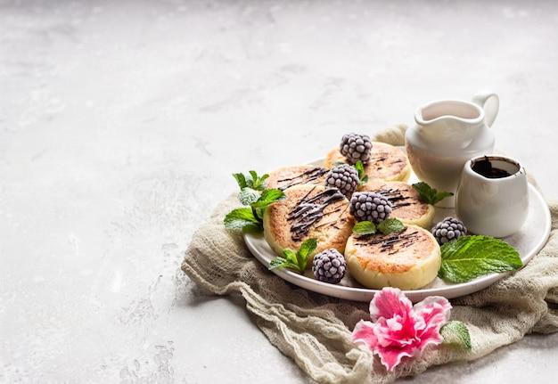 Panquecas de queijo cottage com frutas, chocolate e menta. syrniki. café da manhã gourmet.