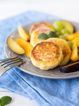 Panquecas de queijo cottage com frutas na parede rústica branca, hora do café da manhã, bolos de queijo caseiros na chapa cinza com pano azul