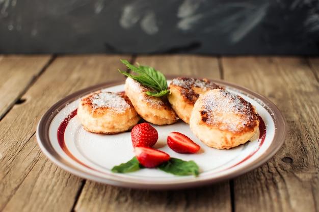 Panquecas de queijo cottage com morangos, menta e açúcar de confeiteiro