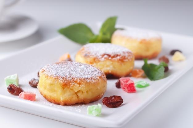 Panquecas de queijo cottage com passas e frutas cristalizadas em uma vista lateral de prato branco