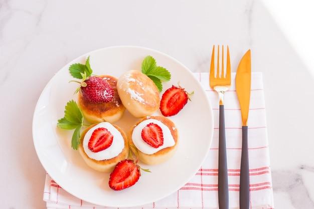Panquecas de queijo cottage doce no prato servido com morangos. syrniki russo, bolinhos de ricota ou bolinhos de requeijão.