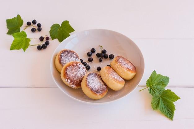 Panquecas de queijo cottage doce no prato servido groselha preta. syrniki russo, bolinhos de ricota ou bolinhos de requeijão.