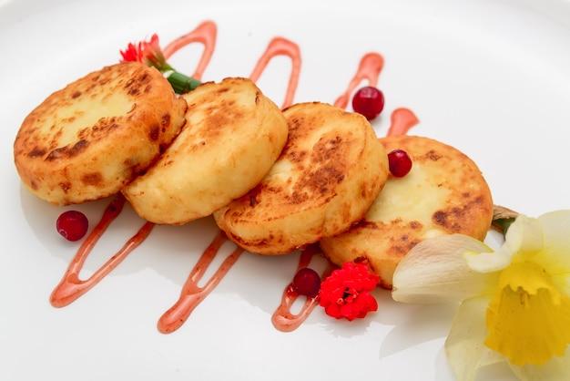 Panquecas de queijo cottage e molho de morango, sobre fundo branco
