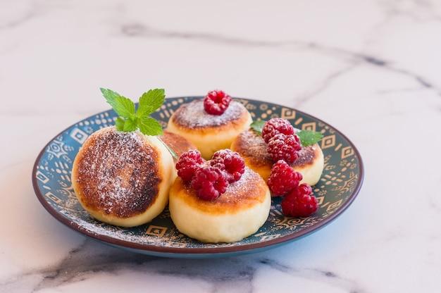 Panquecas de queijo cottage ou syrniki com framboesa e açúcar em pó. café da manhã saudável.
