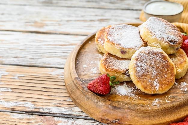 Panquecas de queijo cottage, syrniki, bolinhos de coalhada com morango. café da manhã gourmet. vista do topo. copie o espaço