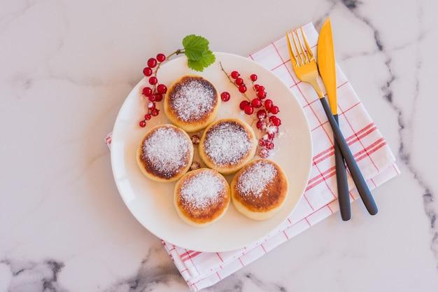 Panquecas de queijo cottage, syrniki, bolinhos de requeijão com frutas frescas de groselha em um prato branco. café da manhã gourmet. foco seletivo