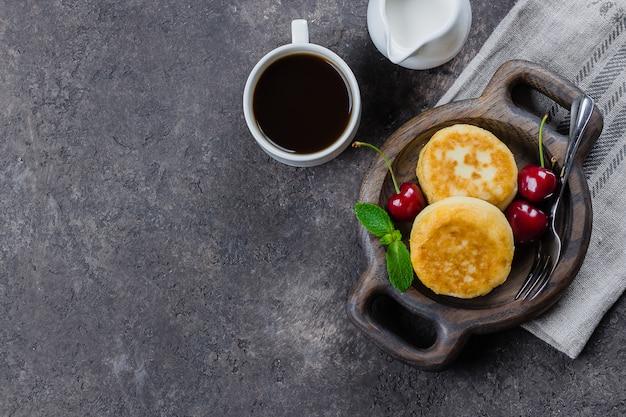 Panquecas de queijo cottage, syrniki, coalhada fritos com cereja