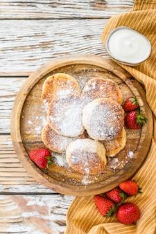 Panquecas de queijo cottage. syrniki com morangos frescos. comida caseira. espaço em branco. vista do topo