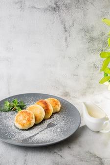 Panquecas de queijo cottage, syrniki ou cheesecakes com creme, mel, hortelã, isolado no fundo branco de mármore. comida caseira. saboroso café da manhã. foco seletivo. foto vertical.