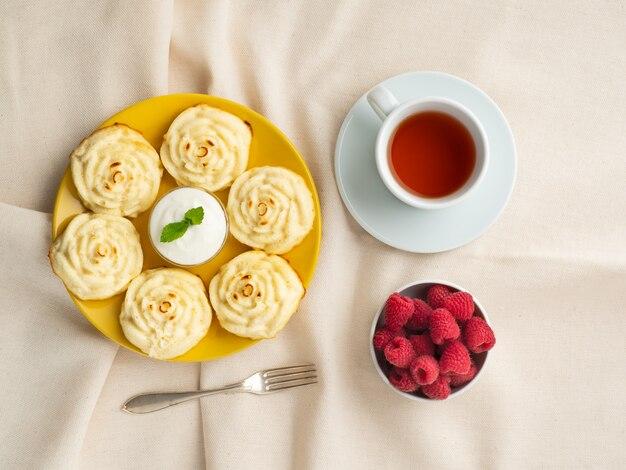 Panquecas de queijo de dieta, forma de rosa, na placa amarela com chá, framboesa. café da manhã de dieta.