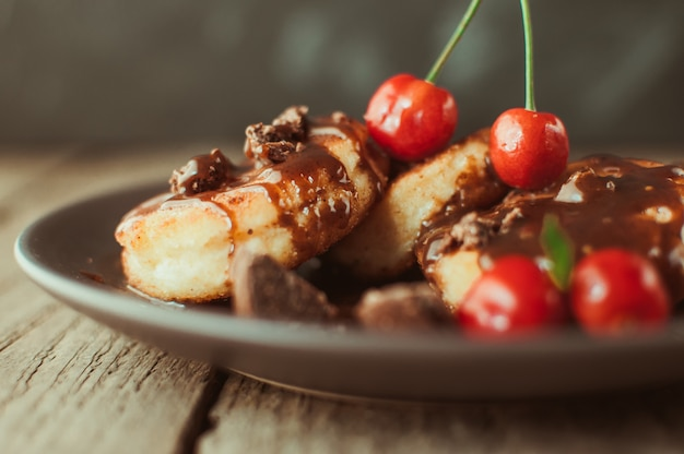 Panquecas de requeijão com cereja e chocolate em um prato marrom