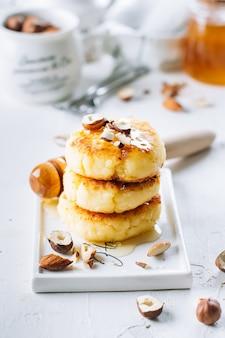 Panquecas de requeijão com mel saboroso e nozes mistas. syrniki, fritos de coalho. fundo branco