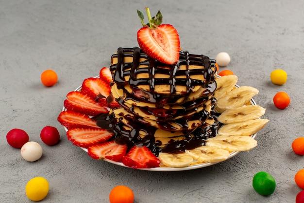 Panquecas de sobremesa de frutas vista frontal com morangos vermelhos em fatias de chocolate e bananas no interior do prato branco sobre o cinza