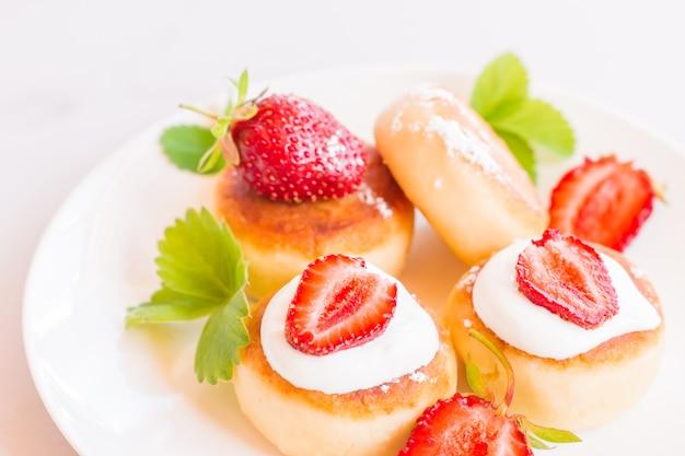 Panquecas de syrniki, requeijão ou queijo cottage com amora, suga em pó sobre uma mesa branca.