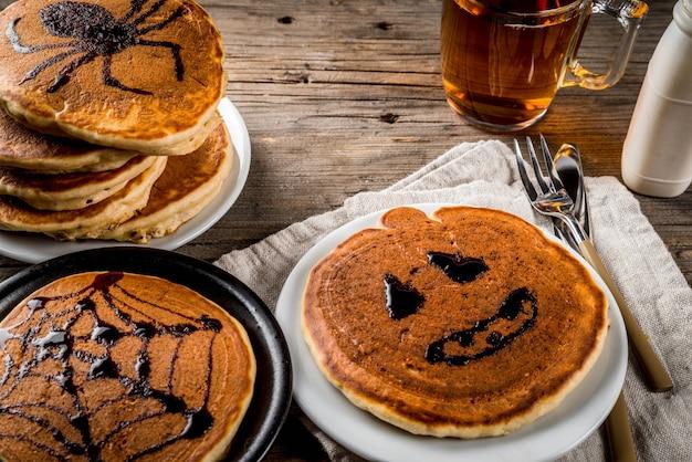 Panquecas de torta de abóbora decoradas com calda de chocolate em um estilo tradicional - teia de aranha, aranha, lanterna de jack