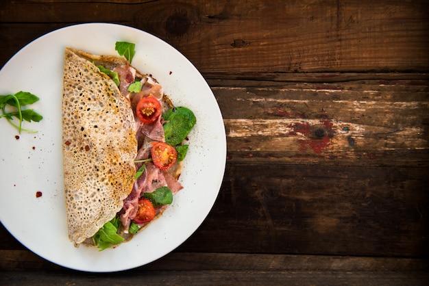 Panquecas de trigo sarraceno com tomate cereja, salada de rúcula, espinafre, presunto de parma