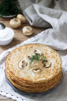 Panquecas de trigo sarraceno servidas com creme de leite e endro em uma mesa de madeira.