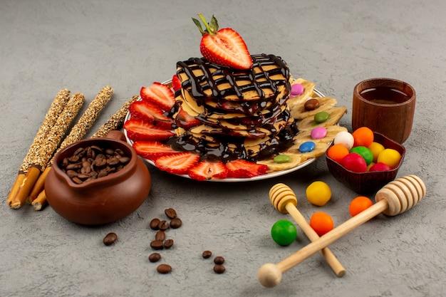 Panquecas de vista frontal gostoso delicioso chocolate com fatias de morangos vermelhos e bananas dentro de chapa branca sobre o fundo cinza