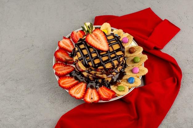 Panquecas de vista superior com frutas frescas e chocolate no chão cinza