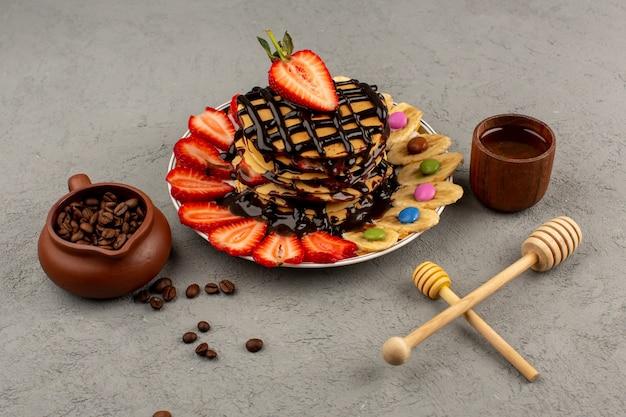 Panquecas de vista superior com frutas frescas e chocolate no cinza