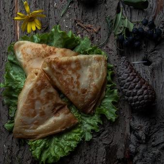 Panquecas de vista superior com queijo em uma salada em uma casca de madeira
