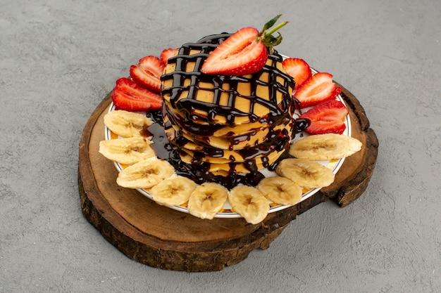 Panquecas de vista superior gostoso delicioso com morangos vermelhos fatiados e bananas dentro de chapa branca sobre o fundo cinza