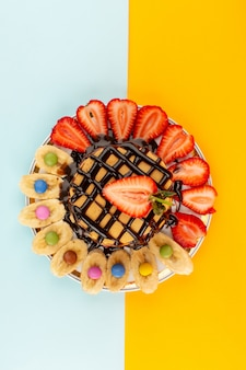 Panquecas de vista superior, juntamente com morangos vermelhos em fatias e bananas, desenhados dentro de um prato branco no colorido