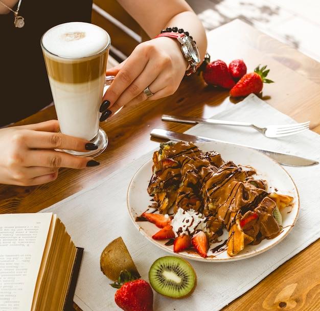Panquecas de waffle de panquecas de vista lateral com chocolate kiwi de morango e macchiato com leite em cima da mesa