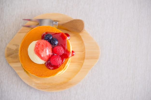 Panquecas deliciosas com a morango no fundo da tabela.