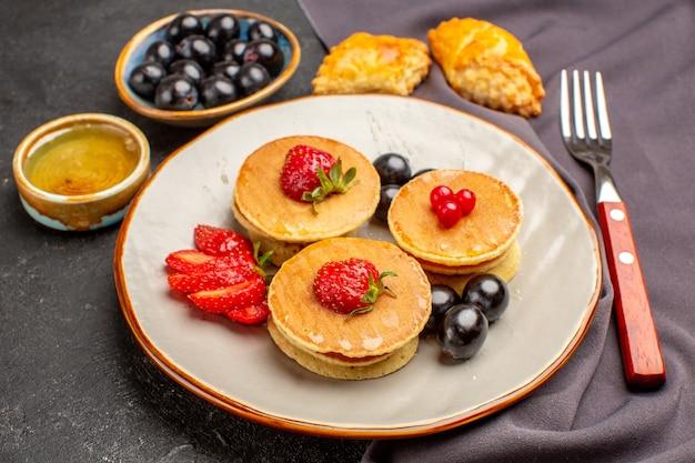 Panquecas deliciosas de frente com azeitonas e frutas no chão escuro bolo de frutas doces