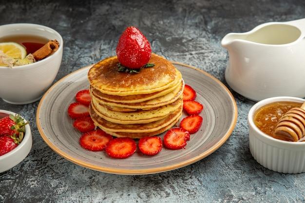 Panquecas deliciosas de frente com frutas e mel em bolos doces de superfície clara