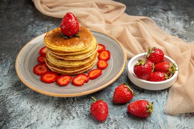 Panquecas deliciosas de vista frontal com morangos frescos em um bolo de frutas doces de superfície clara