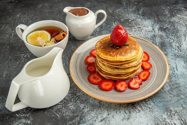Panquecas deliciosas de vista frontal com uma xícara de chá e frutas no bolo de frutas de superfície clara