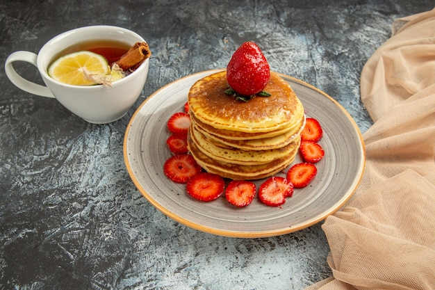 Panquecas deliciosas de vista frontal com uma xícara de chá e frutas no bolo de superfície clara de frutas doces