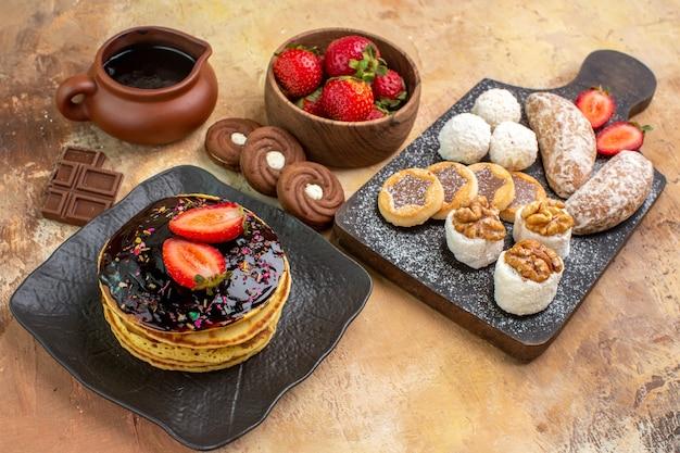 Panquecas doces com bolos e biscoitos na mesa de madeira
