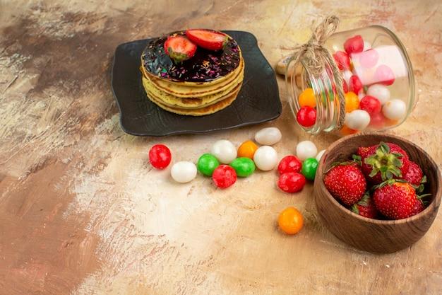 Panquecas doces com doces coloridos em torta de sobremesa de mesa de madeira