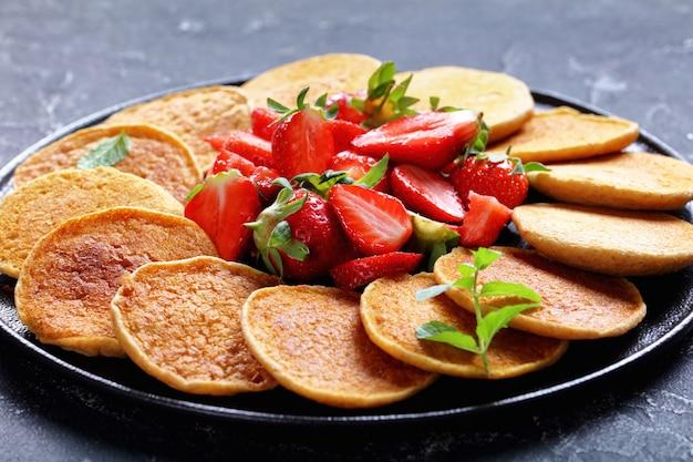 Panquecas doces de aveia frita na hora com morangos e mel em uma placa preta sobre uma mesa de concreto, comida saudável