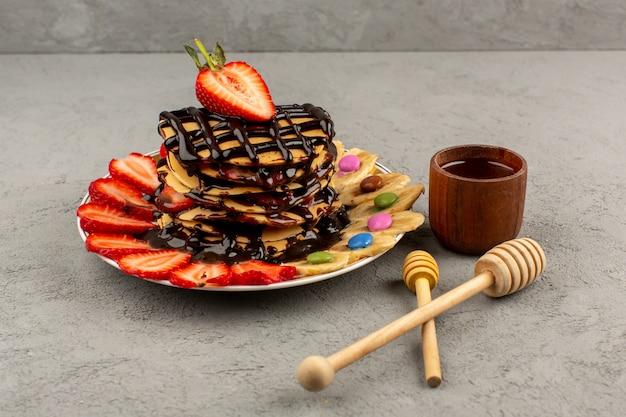Panquecas doces de vista superior com frutas e chocolate no chão cinza