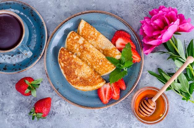 Panquecas doces quentes com morangos frescos