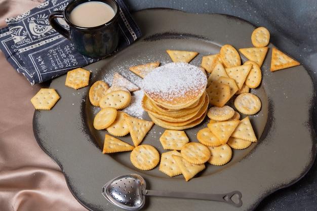 Panquecas e batatas fritas com leite de frente na mesa cinza