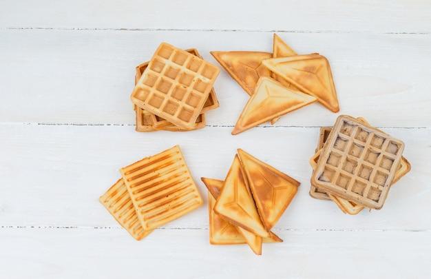 Panquecas e waffles em uma superfície de madeira branca
