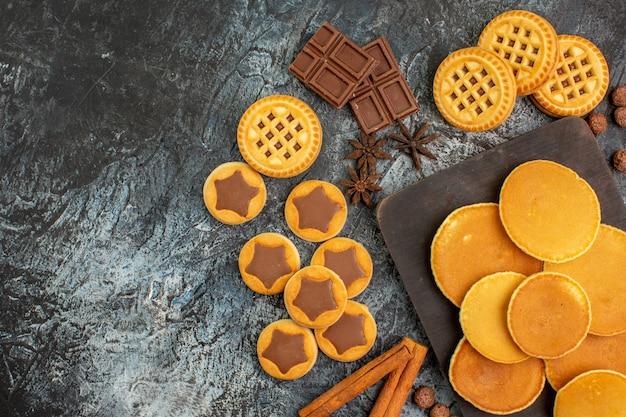Panquecas em travessa de madeira com biscoitos e doces em fundo cinza